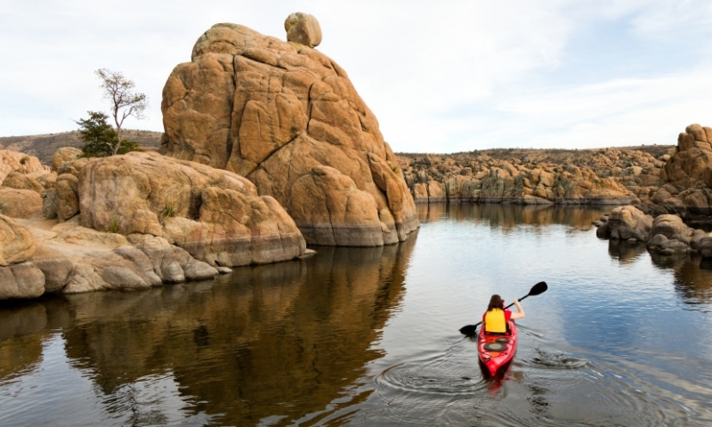 Woman Kayaks the shores of Watson Lake in Prescott Arizona